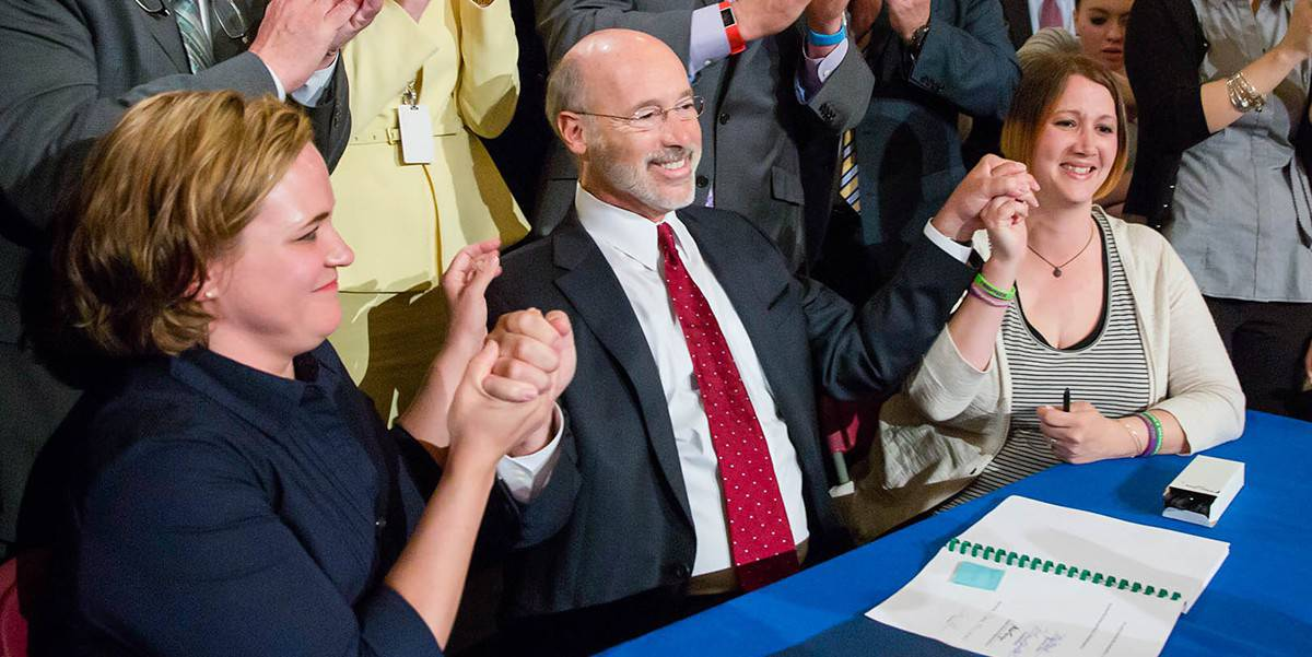 Governor Tom Wolf smiles and holds up his arms after signing a bill legalizing medical marijuana in PA