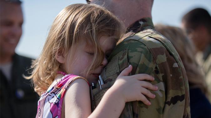 A young girl hugs a National Guard service member
