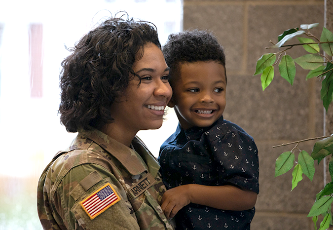 A female member of the National Guard holds a smiling boy.